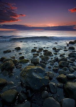Pink Clouds At Sunset With The Surf Rolling Into The Rocks Along The Coast Of A Hawaiian Island, Hawaii, United States Of America