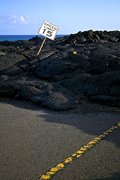 Speed Limit Sign Bending To The Side In The Black Lava Rock On The Coast, Hawaii, United States Of America