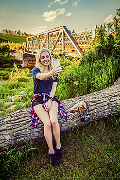 A young woman sits on a log in a park taking a self-portrait with her cell phone with a bridge and river in the background, Edmonton, Alberta, Canada