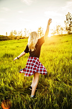 A young woman with long blond hair twirls and runs freely in a grass field in a park at sunset, Edmonton, Alberta, Canada