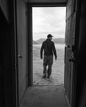 A man and the Valley of Ten Thousand Smokes is framed by the doorway of one of the Baked Mountain Huts in Katmai National Park, Alaska, United States of America