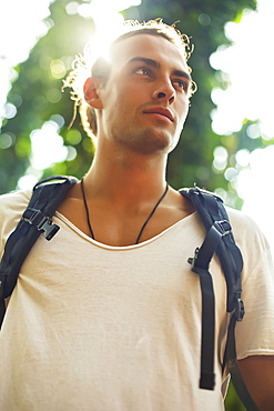 Low angle view of a young man wearing a backpack with the sun behind him, Hawaii, United States of America