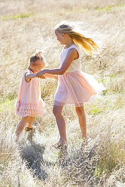 Two Young Girls Dancing In A Field Of Long Grass, Washington, United States Of America