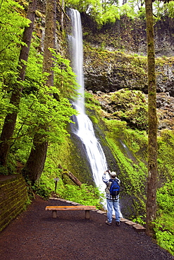 A Hiker Taking A Picture With His Camera At Winter Falls In Silver Falls State Park; Oregon, USA
