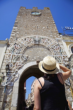 Female Tourist Looking At The Clock Tower Of San Giuseppe Church; Taormina, Sicily, Italy