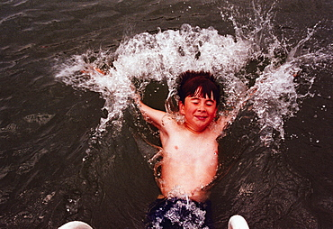 a young boy splashing in the water