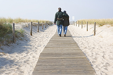 A couple walking down a pathway to the ocean