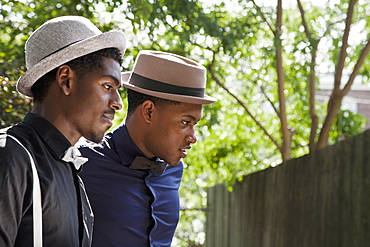 Two young black men dressed in bow ties and hats, looking away