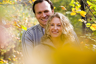Mid adult couple embracing between branches with autumn leaves