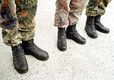 Three army soldiers standing in a row