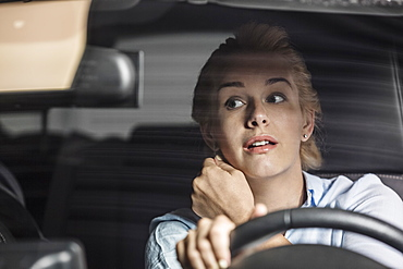 Mid adult woman looking in rear-view mirror while driving car