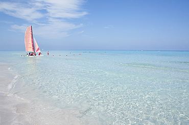 Mid distance view of people traveling in sailboat on sea against blue sky