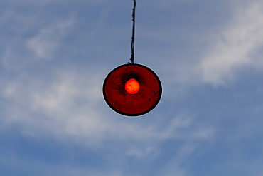 Low angle view of lamp hanging against cloudy sky