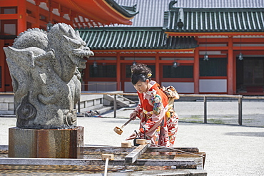 Mid adult woman washing hand against temple