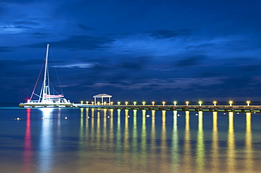 Sailboat moored at illuminated pier on lake against sky at night