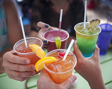 Cropped image of people holding drinks outdoors
