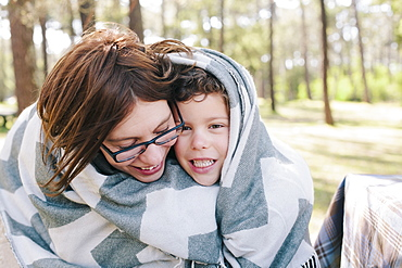 Happy mother and son wrapped in blanket at forest