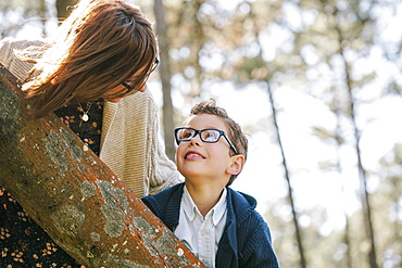 Loving mother and son looking at each other in forest