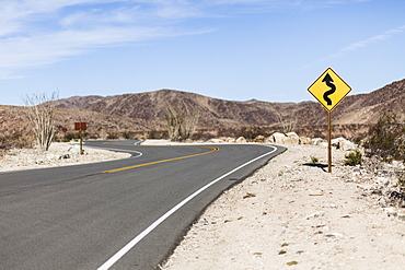 Directional sign by road at Joshua Tree National Park against sky