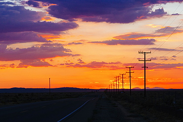 Country road and silhouette field against cloudy sky during sunset
