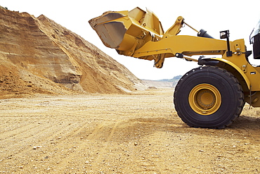 Earth mover loaded with sand on field