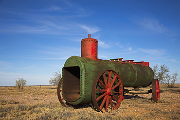 Abandoned steam engine on field against blue sky