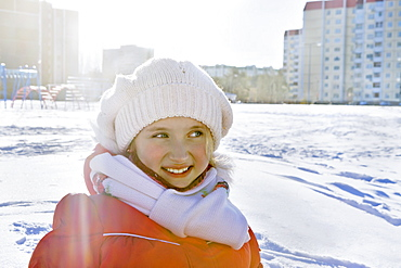 Smiling girl in winter clothes in snowy city park