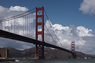 Low angle view of Golden Gate Bridge over river against cloudy sky