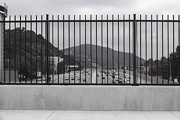 Mountain and street seen through fence against sky