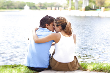 An affectionate couple kissing by a lake, rear view