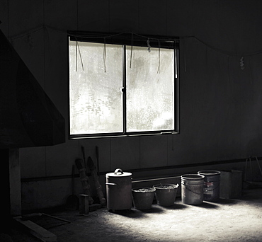 Row of containers by window in abandoned room