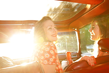 Two rockabilly women having fun in the front seat of a vintage car