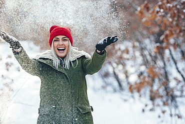 Portrait of happy young woman playing in snow