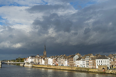 Meuse River by houses in city against cloudy sky