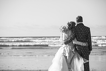 Rear view of bride and groom standing arm around at beach