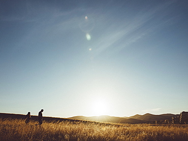 Couple walking on field against sky during sunny day
