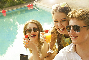 Cheerful woman holding drinks while sitting with male friend at poolside