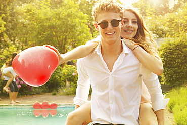 Portrait of happy man piggybacking woman holding heart shape balloon at poolside