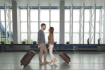 Full length side view of young couple with luggage looking at each other at airport
