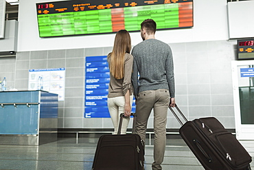 Rear view of young couple looking at flight-information board at airport