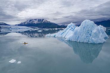 Person canoeing in lagoon by icebergs against cloudy sky, Lake George, Palmer, Alaska, USA