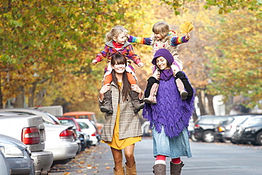 Two mothers with their daughters on their shoulders in prenzlauer berg, berlin, germany