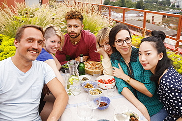 Portrait of happy male and female friends sitting at outdoor table at patio