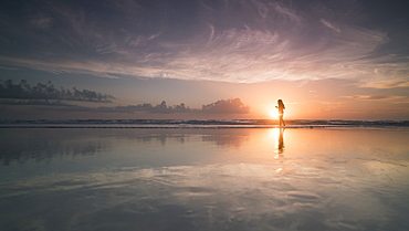 Silhouette woman at sea shore against cloudy sky during sunset, Daytona, Florida, USA