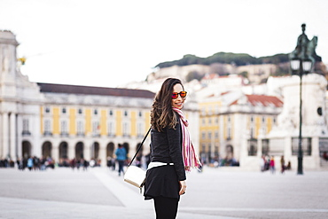 Smiling mid adult woman standing at town square against building in city, Lisbon, Portugal