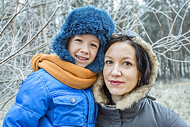 A cheerful mother and son in warm clothing outdoors in winter