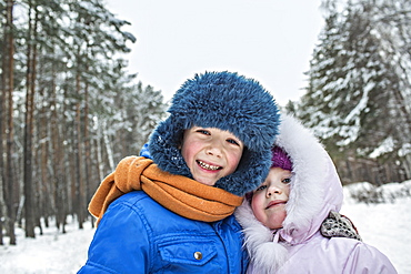 A cheerful brother and sister in warm winter clothing outdoors in winter