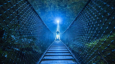 Mysterious silhouetted person on suspension bridge in woods at night