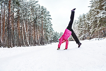 A woman doing a cartwheel in the snow