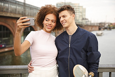 Young couple with smart phone taking selfie on bridge